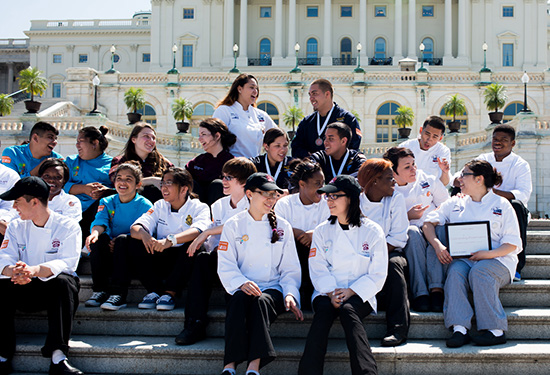 A group of student chefs sit on the steps of the United States White House