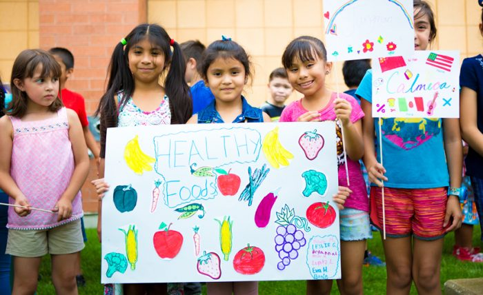 children outside holding signs about healthy school food