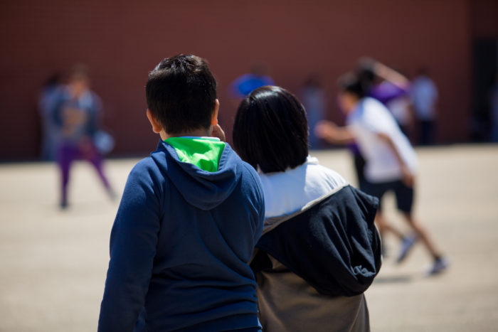 two students looking at peers on a school playground
