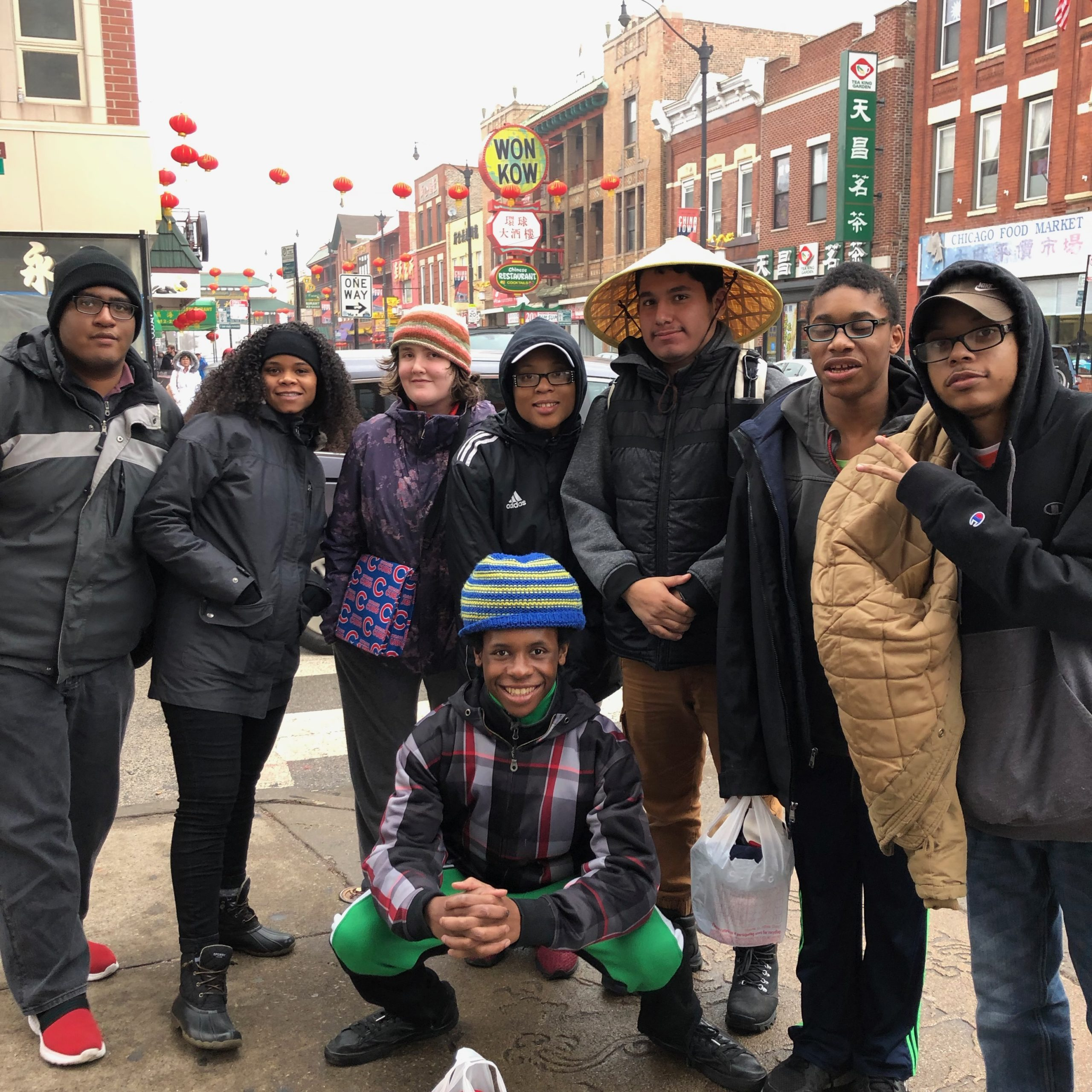 8 high school students stand outside on a city street.