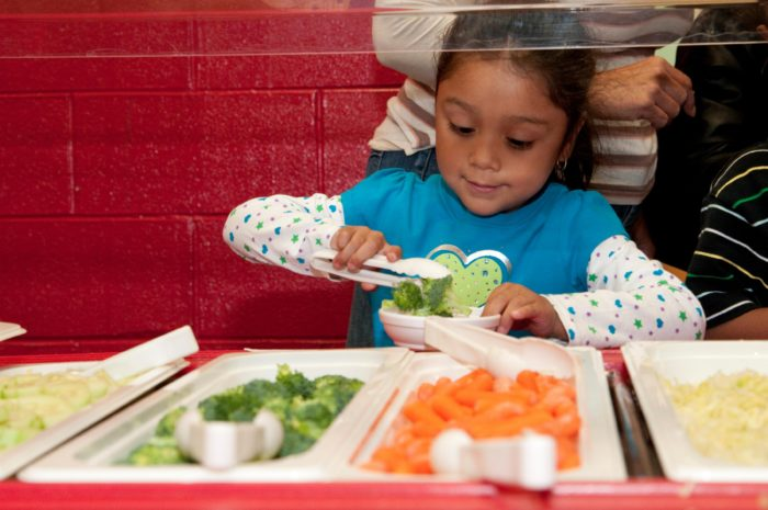 A young girl places food on her plate from trays of vegetables.