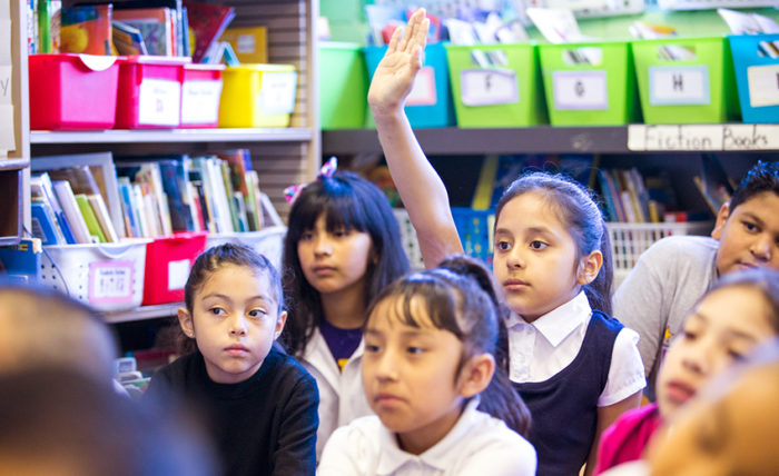 children in classroom with one raising her hand