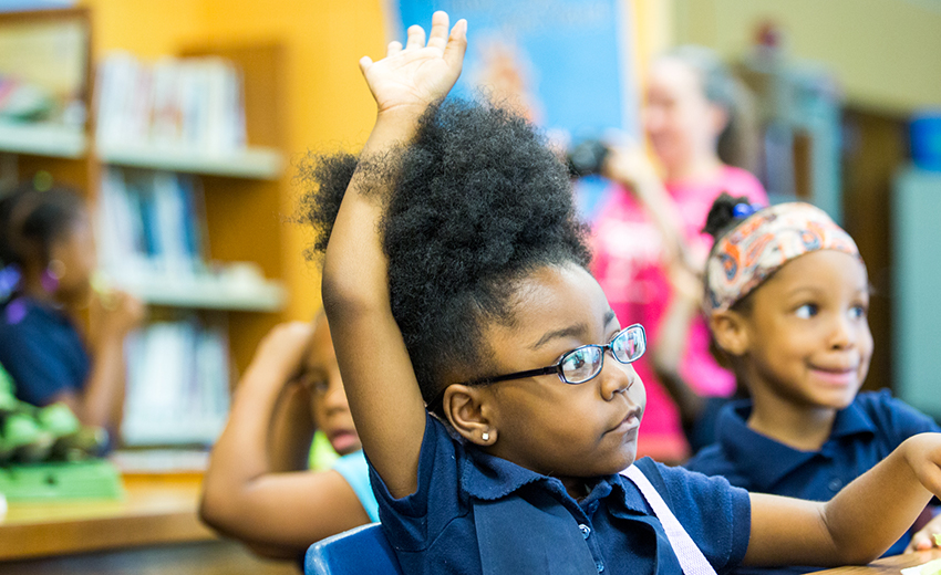 Young Girl Raising Her Hand In Chicago Classroom