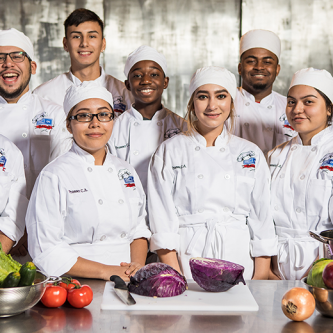 Prosser High School students chefs posing with fresh produce at Cooking up Change 2017 in Chicago