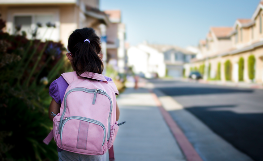 Back Of Young Girl Wearing Backpack Standing On Empty Street
