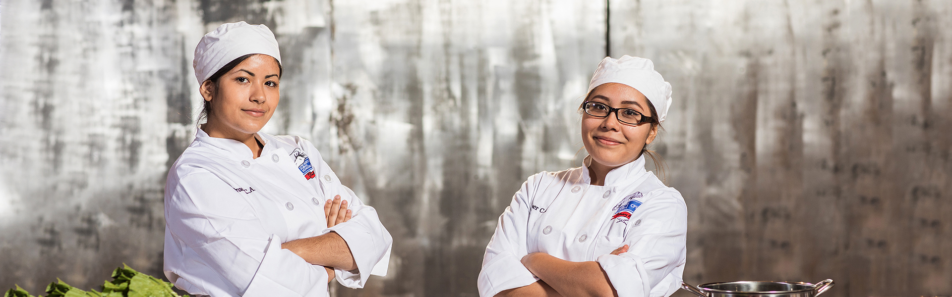 two female culinary student chefs at Cooking up Change posing in front of a grey background