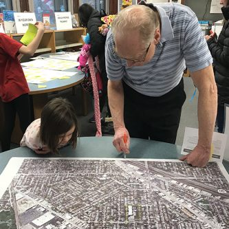 older man and young student writing on a map at a Farnsworth Space to Grow planning meeting