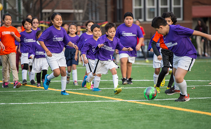 Latino students playing soccer on the Space to Grow schoolyard at Gunsaulus in Chicago