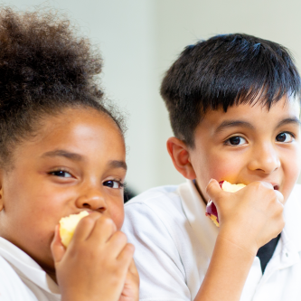A girl and a boy eat apples while smiling.