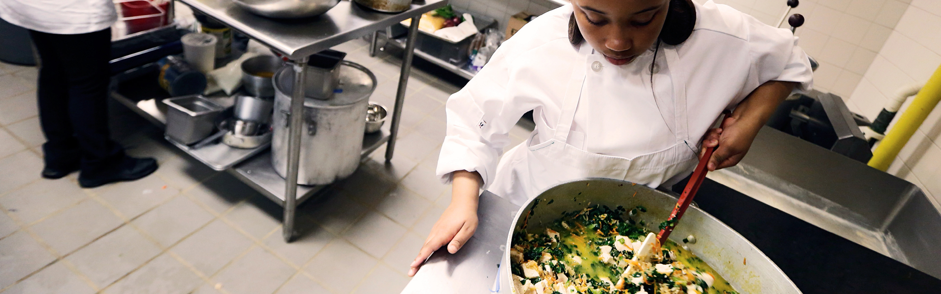 A girl in a chef's uniform and apron stirs a pot of vegetables and tofu in an industrial kitchen.