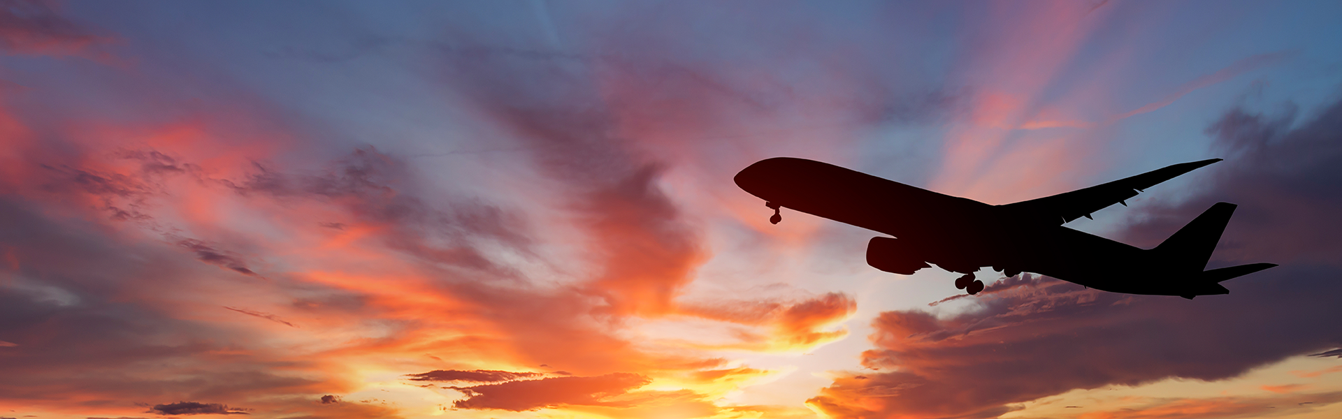 From below, the sihlouette of an airplane ascending toward a partly cloudy sky at sunset.