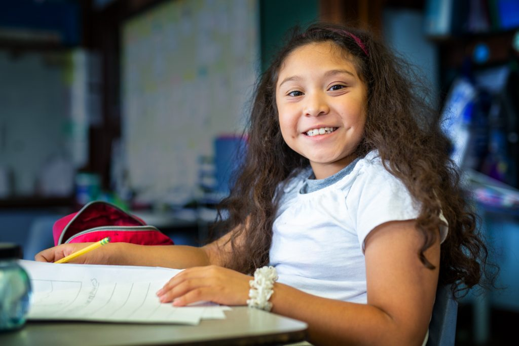 A girl smiles at us and sits at a school desk. She holds a piece of paper in her left hand and a pencil in her right hand.