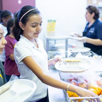 Two girls select fruit and lunch food items at a school cafeteria counter